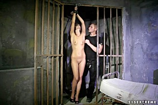 Tall and slender brunette Sophie Lynx is being tied up in the cage and rudely fucked up by two guardian dudes.