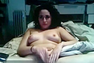 Curly haired brunette girl watches porn, masturbates and orgasms.